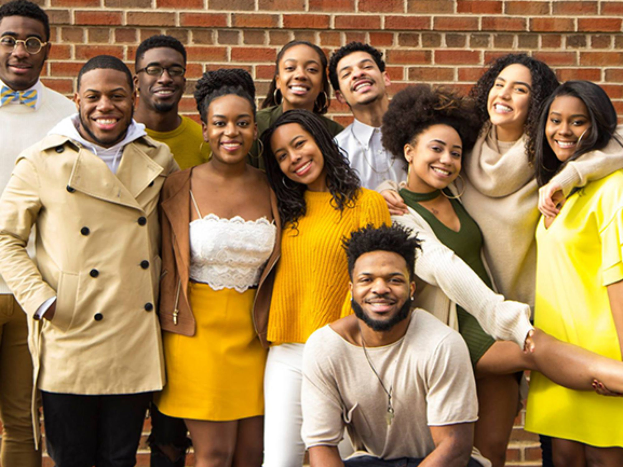 Members of Black Student Alliance smiling in front 的 a brick wall.