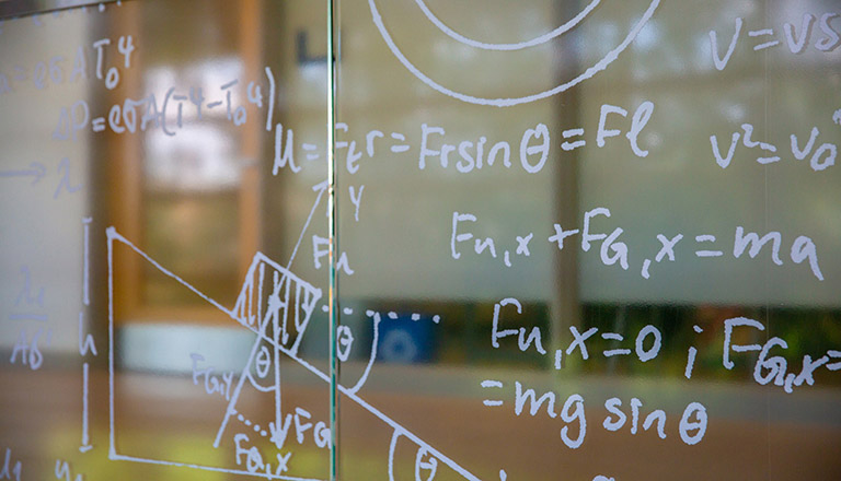 Mathematical functions written on a whiteboard.