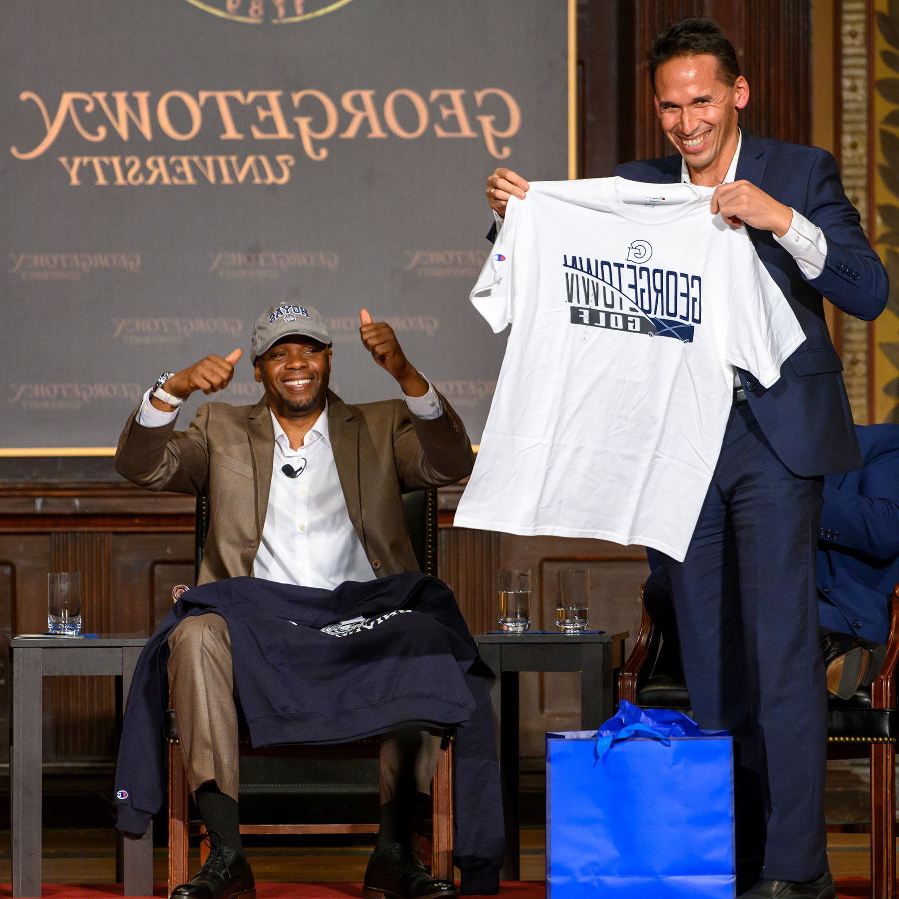 Professor Marc Howard stands on stage in Gaston Hall, presenting a 365体育备用网址 golf t-shirt to Valentino Dixon.