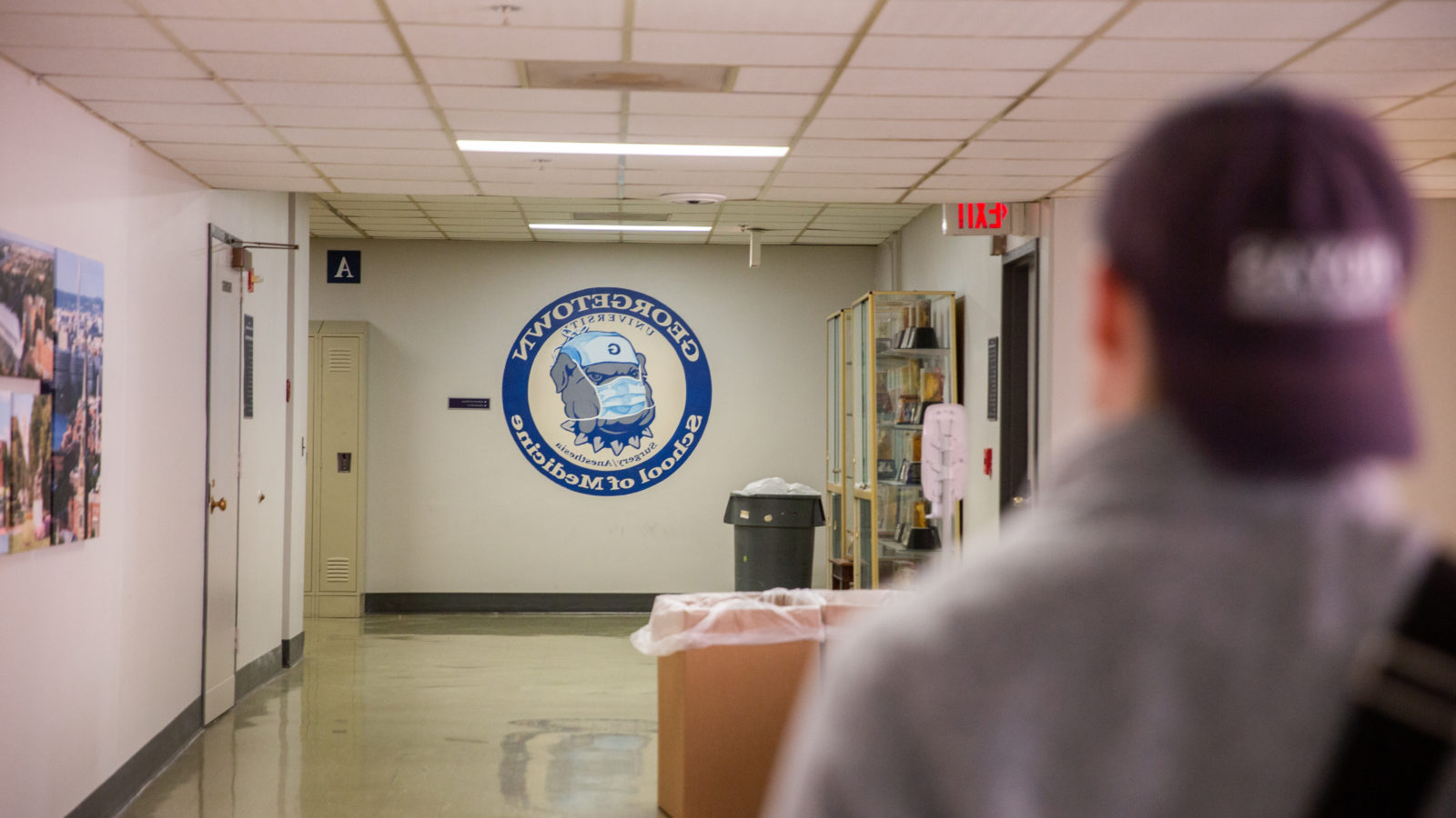 A student with a blue hat on backwards walks down a hallway, at the end of which a logo for the School of Medicine is painted on the wall.