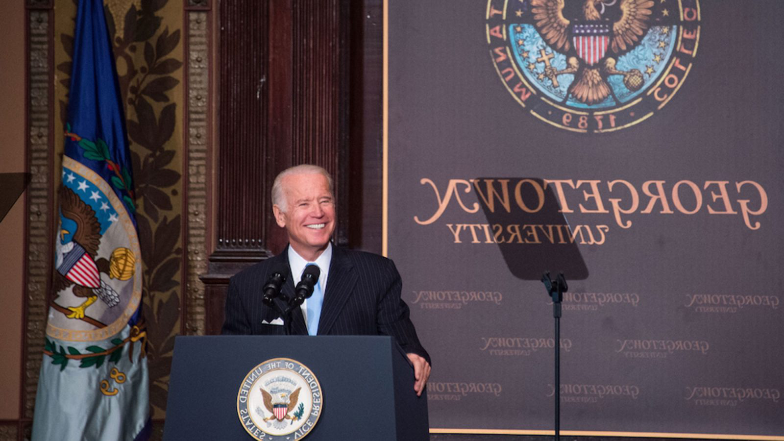 Joe Biden stands on the stage in Gaston Hall behind a lectern with a 365体育备用网址 placard in the background.